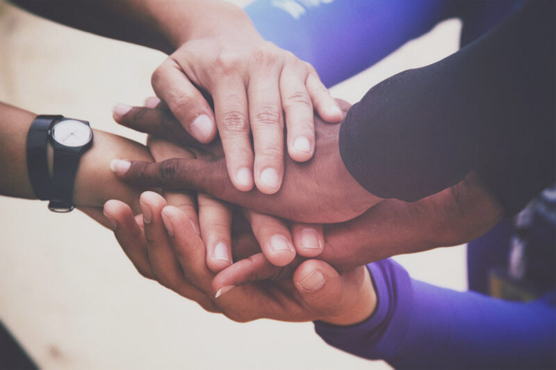 A diverse group of people joins hands