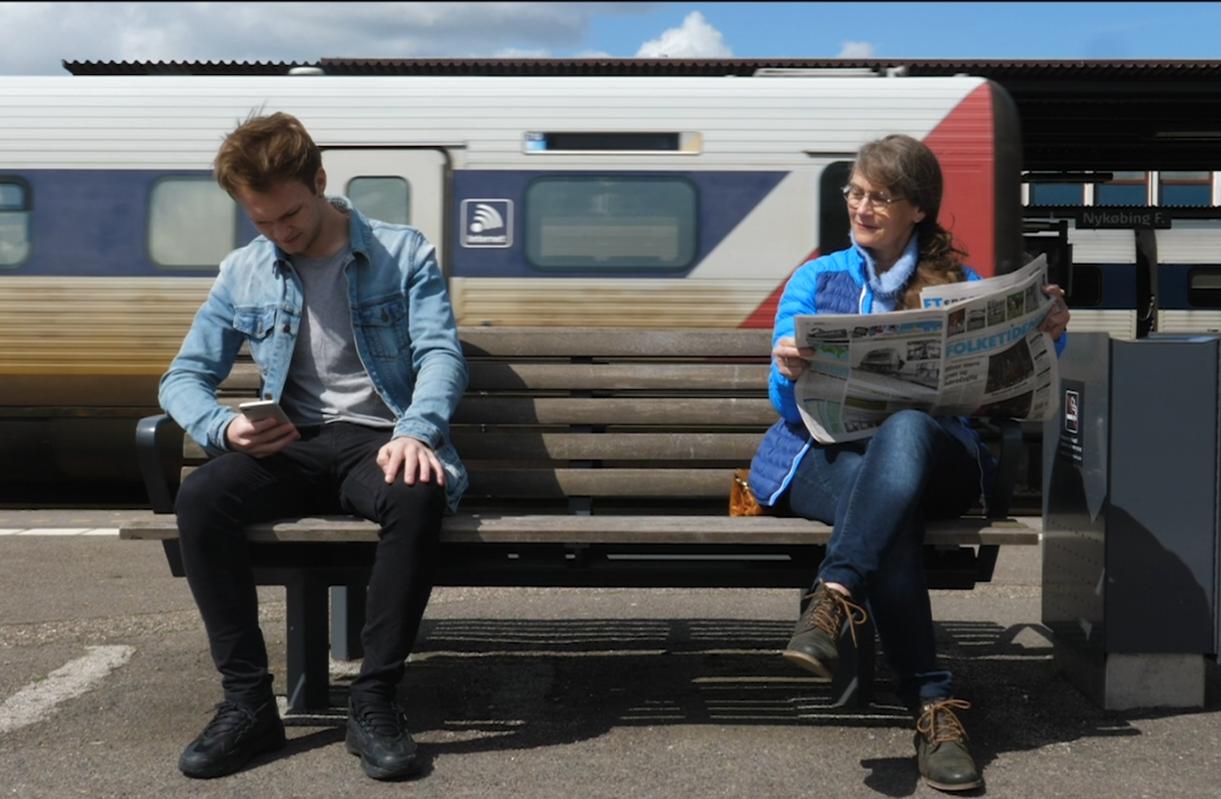 Ung mand med mobil sidder på en bænk på en togstation. Ved siden af sider en ældre kvinde med en Folketidende avis og smiler mens hun kigger mod hans telefon.
