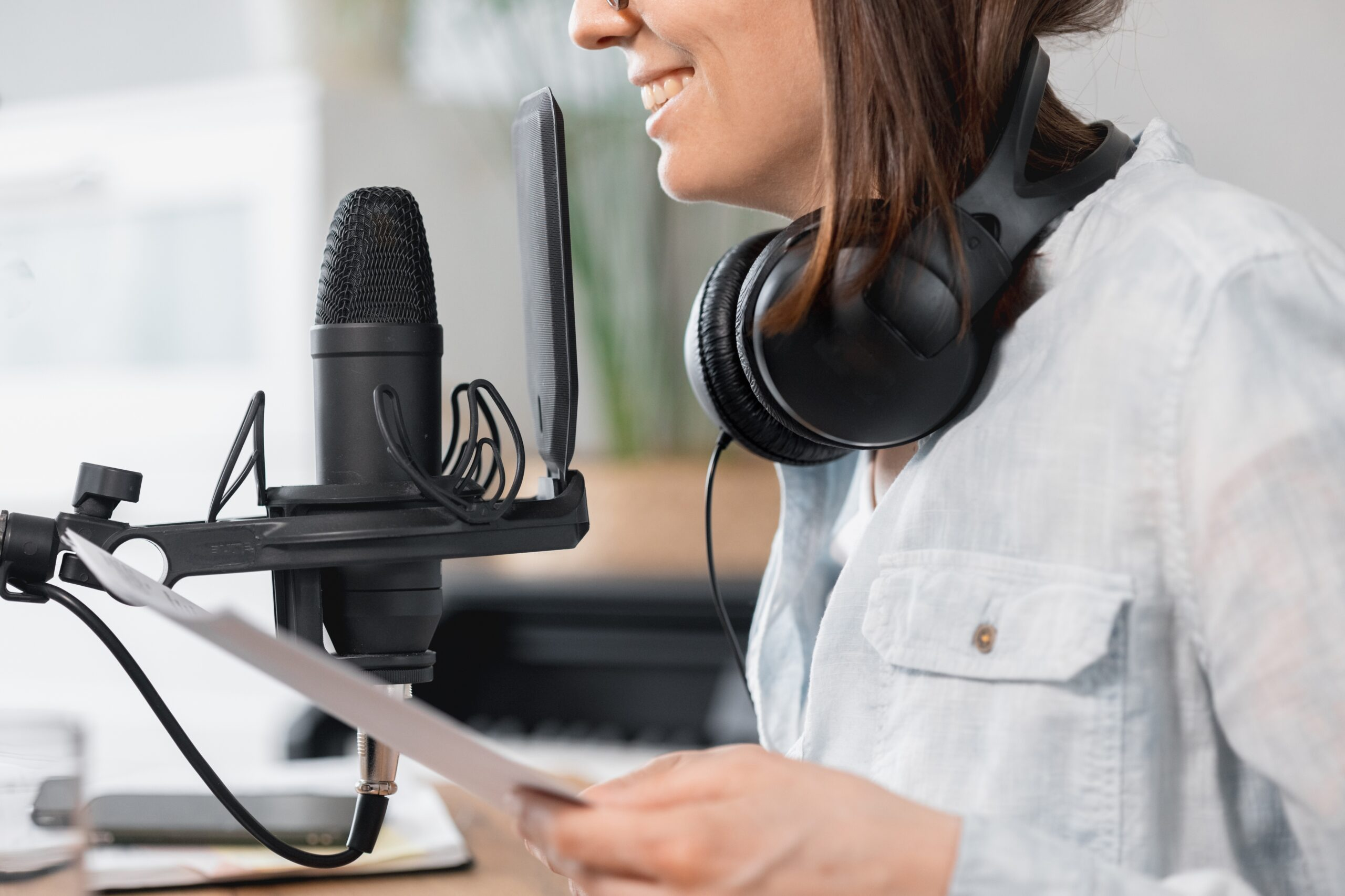 caucasian-millennial-woman-with-a-microphone-and-headphones-recording-a-podcast-in-a-recording-studio_t20_3grer2
